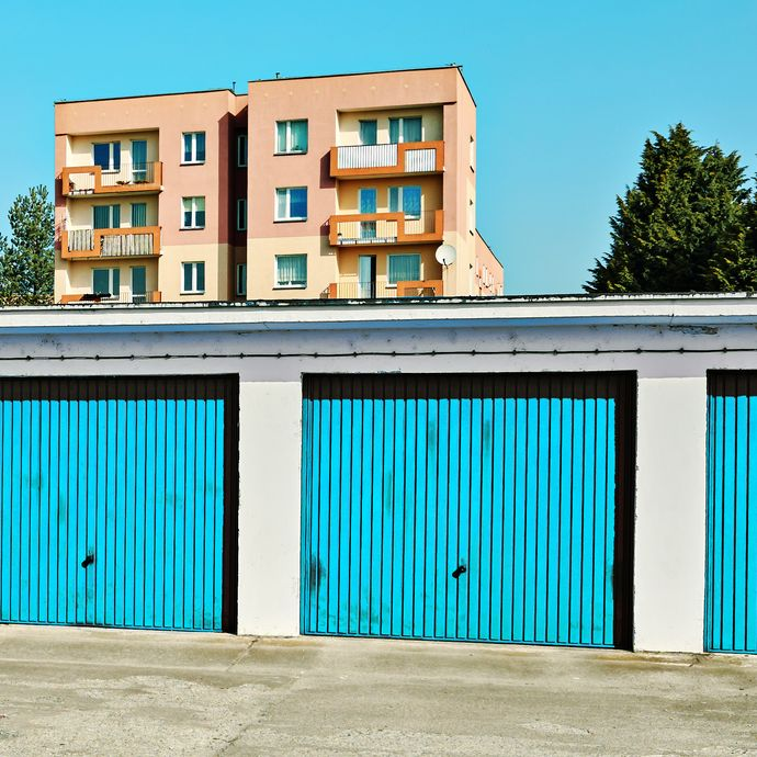 Garages with blue doors and buildings behind