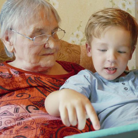 Grandparent and child learning on a digital tablet